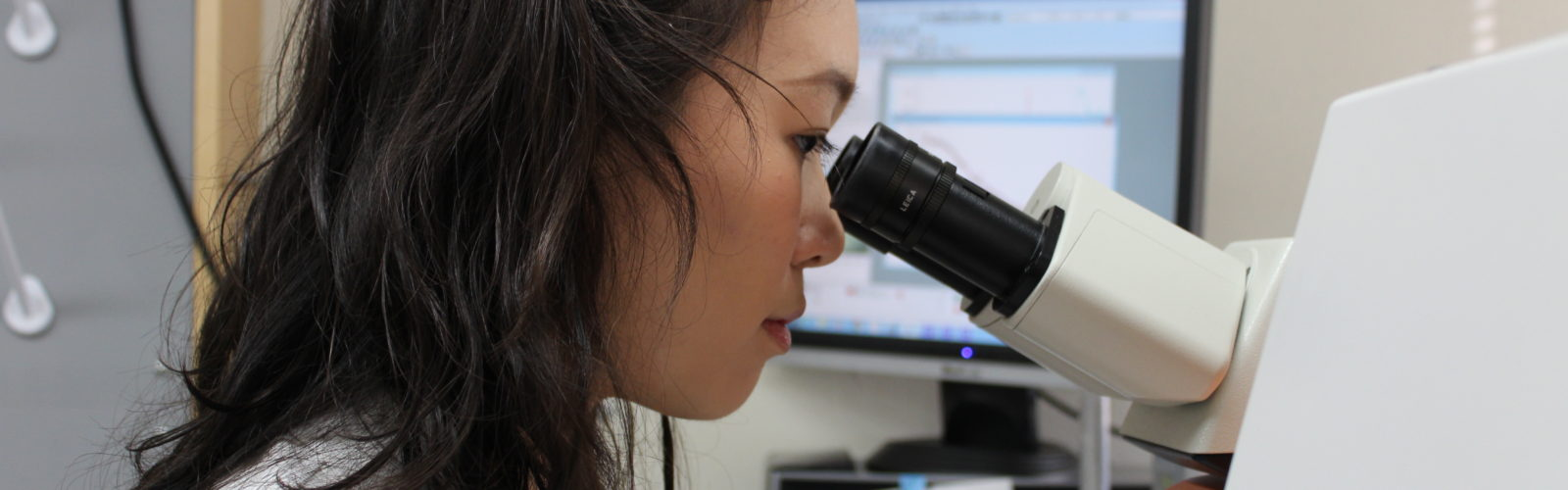 Student researcher looking through a microscope.