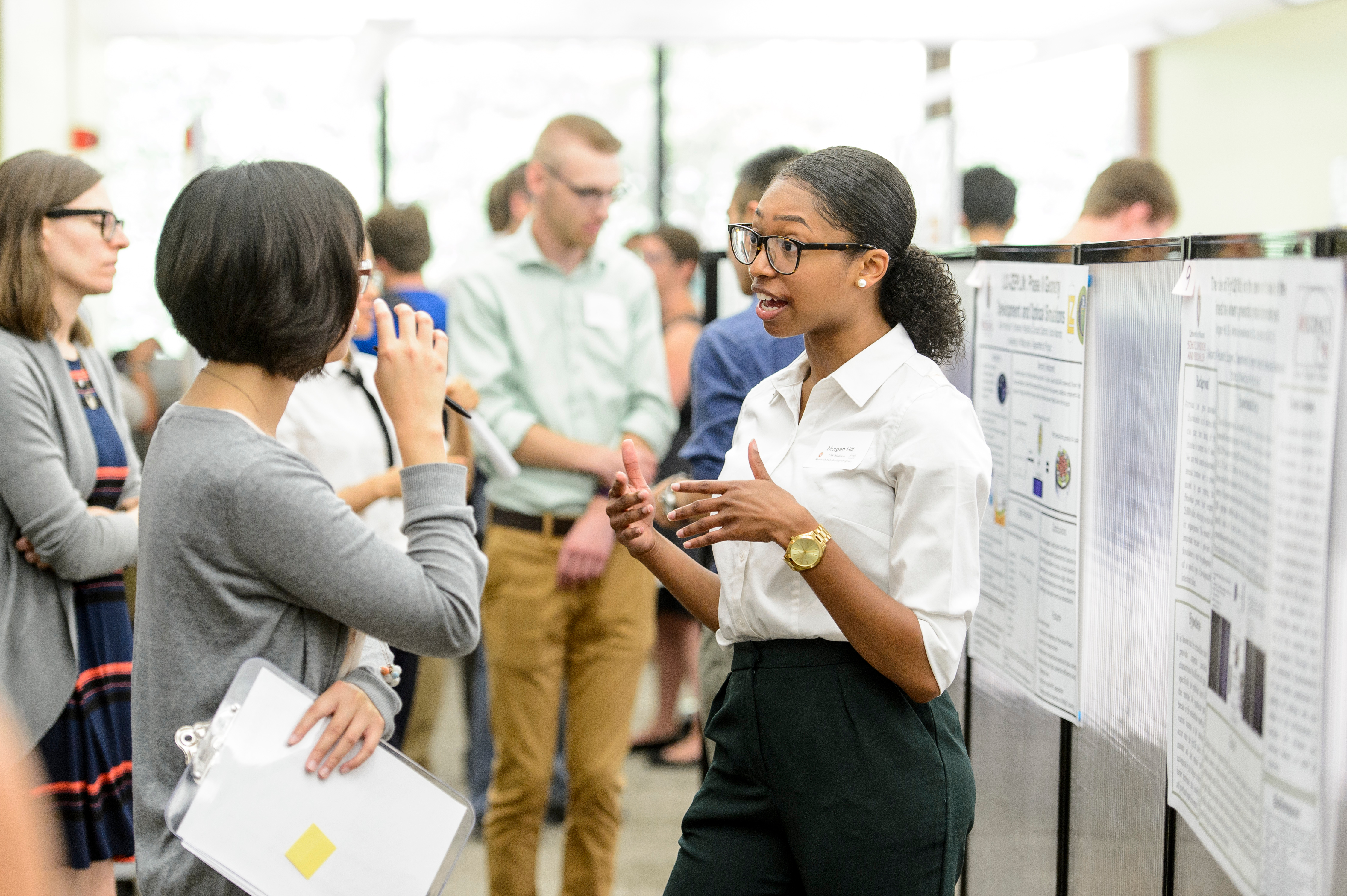 Student presents a poster at summer research poster session