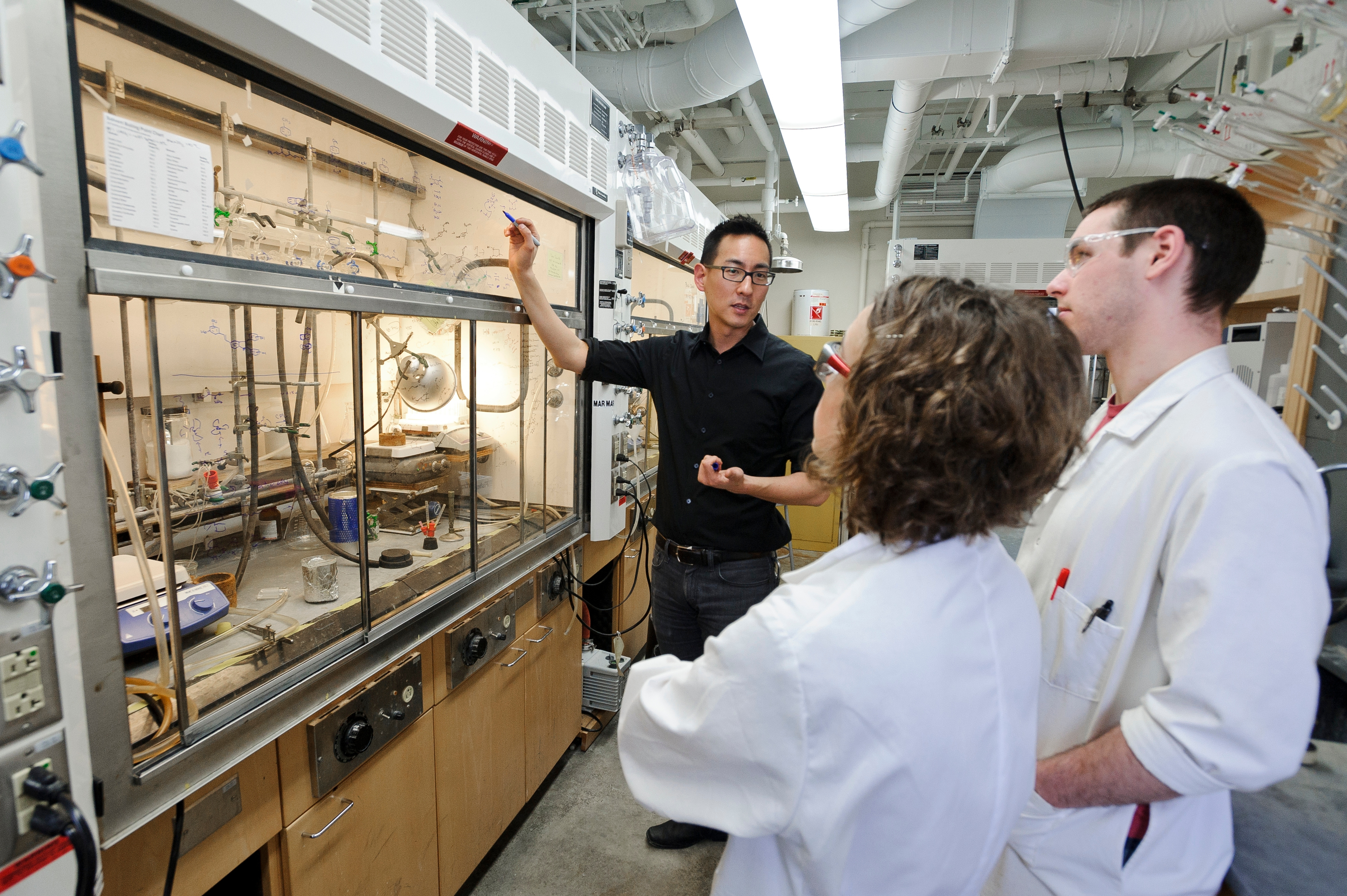 Prof. Yoon speaking with two students in the lab in front of a chemical fume hood